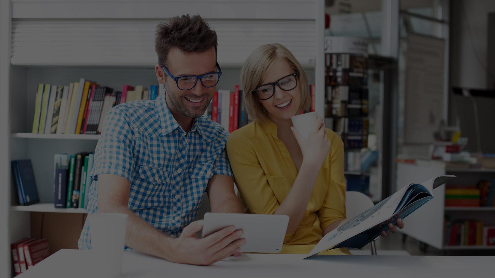 homme et femme qui regardent l'écran d'une tablette
